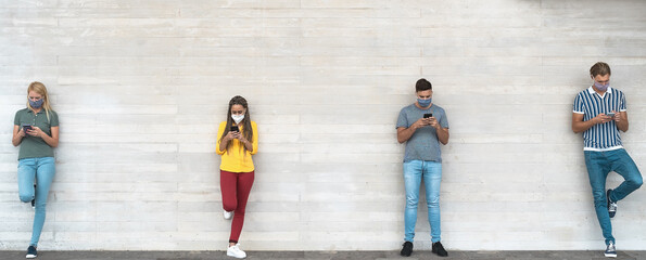 Young people wearing surgical mask using mobile phone keeping social distance - Millennial friends watching media trends on smartphones during corona virus outbreak - Youth and technology concept
