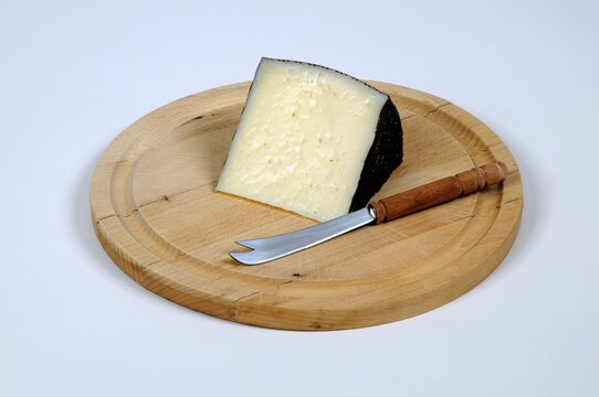 Wedge of Manchego cheese on a wooden cutting board, Spain.