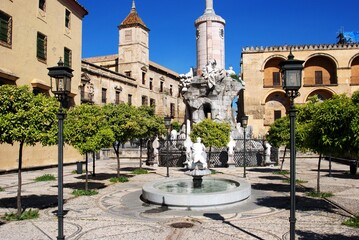 Garden with fountain and San Rafaels Gate Bridge Triumph Monument with the Episcopal Palace to the rear, Cordoba, Andalusia, Spain.