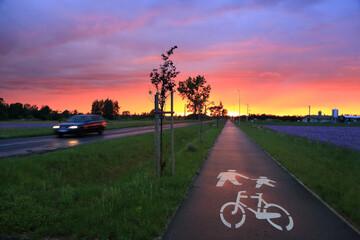 Kolorowy zachód słońca nad polami i ścieżką rowerową wieczorem.