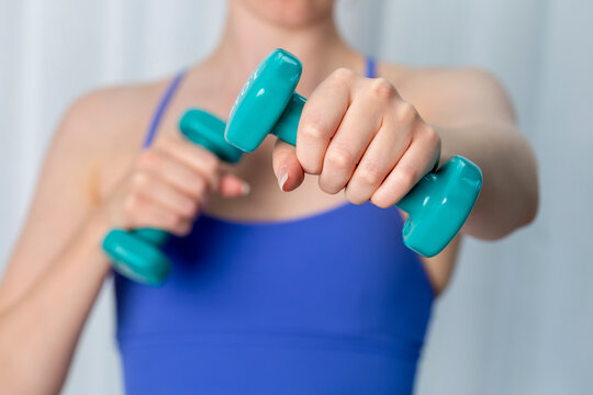 Young woman exercising at home in blue sports top using dumbells