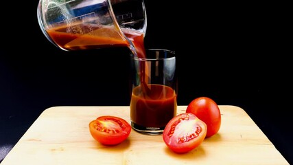 Fototapete - Pour homemade tomato juice into a glass on wooden board