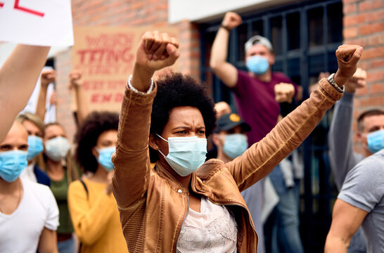 African American woman wearing protective face mask while protesting with arms raised on city streets.