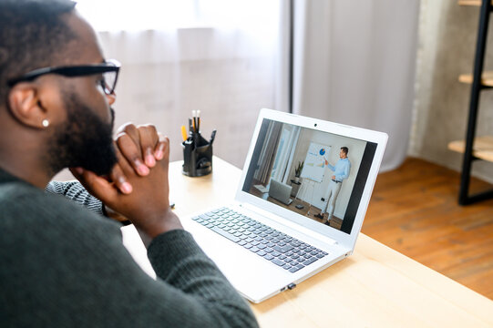 Concentrated guy in glasses using laptop for online learning, studying. A black guy sits at the desk and watches online video classes or webinars with male teacher on the laptop screen, side view