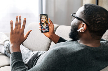 Happy african-american guy is talking via video with female friend or employee on smartphone. A black guy is laying on the sofa in cozy living room and waving hello on phone screen