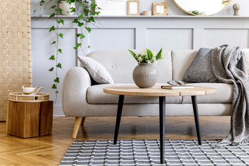 Scandinavian concept of living room interior with design sofa, coffee table, plant in pot, lamp, carpet, plaid, pillow, shelf, decoration and personal accessories in modern home staging.
