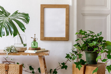 Trendy composition of home garden interior with mock up poster frame, wooden bench, plants in design pots, tropical leaf in vase, decoration, personal accessories in stylish home decor.