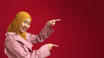 Portrait of attractive beautiful muslim teenage girl wearing hijab  smiling and pointing to the side with copy space, presenting something, marketing concept