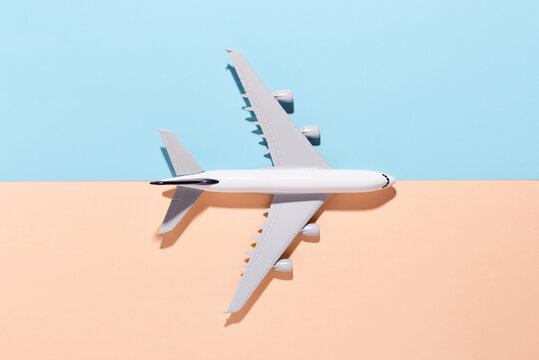 Model airplane on light blue and orange color paper background. Flat lay, top view and copy space for your text