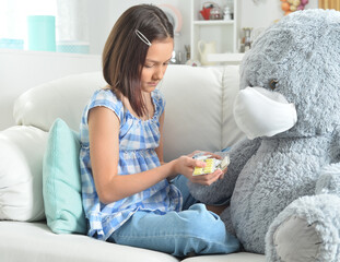 Girl giving pills to toy bear in facial mask on sofa