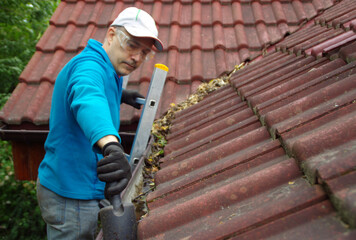 Man on ladder cleans gutter on the roof