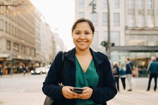 Portrait of smiling female entrepreneur with phone standing in city