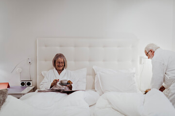 Smiling senior woman having coffee while man standing by bed in hotel room