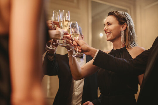 Multi-ethnic group of people toasting champagne at party
