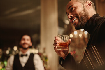Man at nightclub with a glass of whiskey
