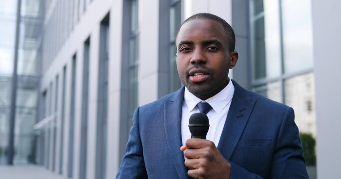 Portrait of young African American handsome male journalist talking with microphone for news episode outdoor. Pandemic concept. Close up of man correspondent in suit and tie and with mic.