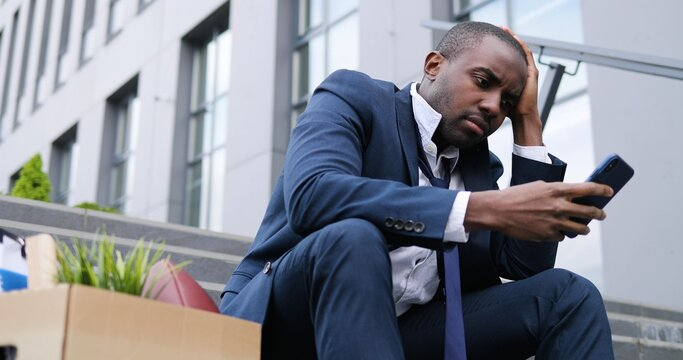 African American businessman sitting on stairs outdoors with box of personal office stuff. Angry despaired male lost work place and texting message on smartphone. Fired man scrolling, tapping on phone