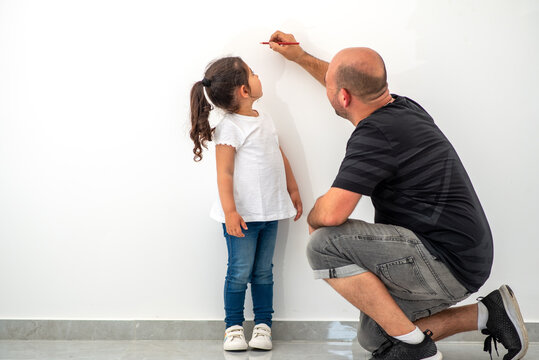 Father measuring height of a cute child. Dad measures the growth of her child daughter at a blank white wall.