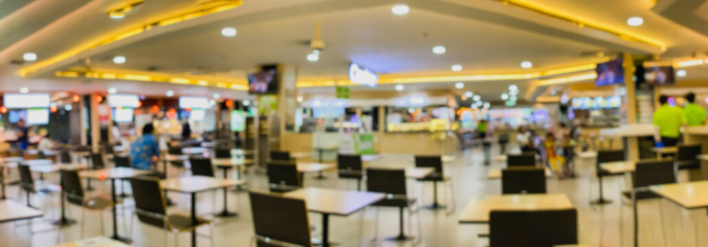 Defocused restaurant in shopping mall with social distancing table pattern