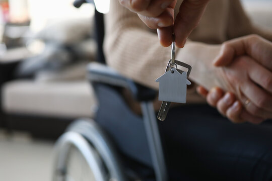 Close-up of persons hand giving keys from new apartment to disabled female. Woman sitting in wheelchair. Moving day into apartment. Handicapped and real estate concept