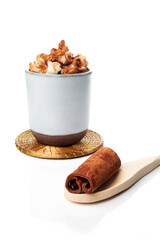 Amazing view of gourmet cinnamon and coffee popcorn with rustic utensils over a white background.