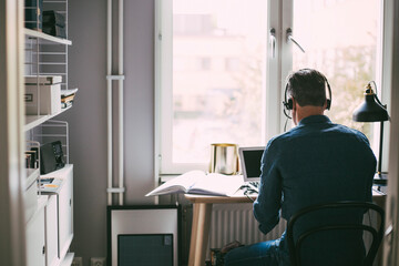 Rear view of man in office at home with headphones