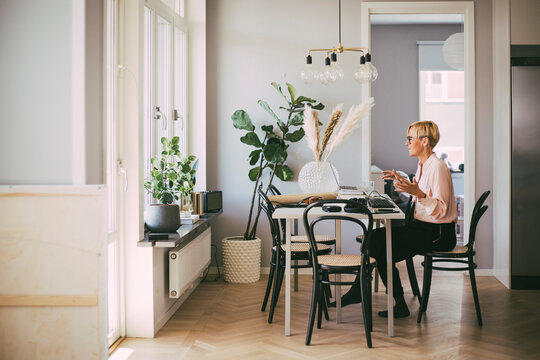 Woman sitting at table having an online meeting working at home