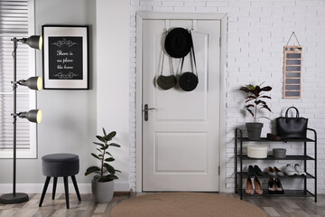 Hallway interior with stylish furniture, shoes and plants