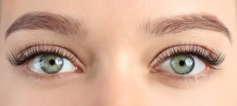 Young woman with beautiful eyelashes after extension procedure, closeup. Banner design