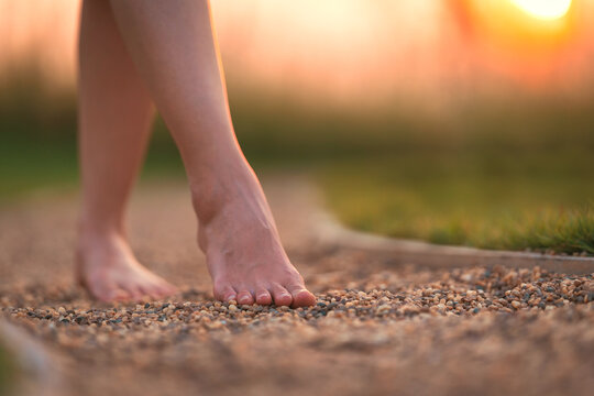 barefoot girl walking on the walkway ground stone with sunset light shine