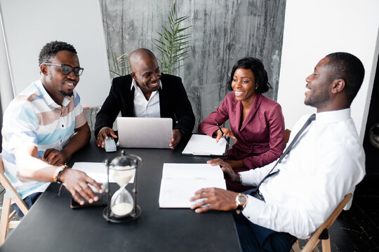 Dark skinned members of the board of directors discuss the company's development strategy in office