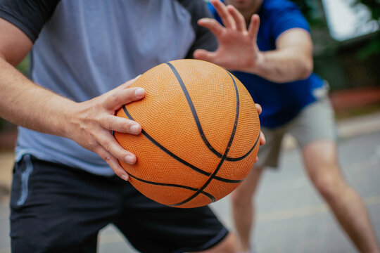 Close up of hands holding ball. Friends playing basketball in the park.