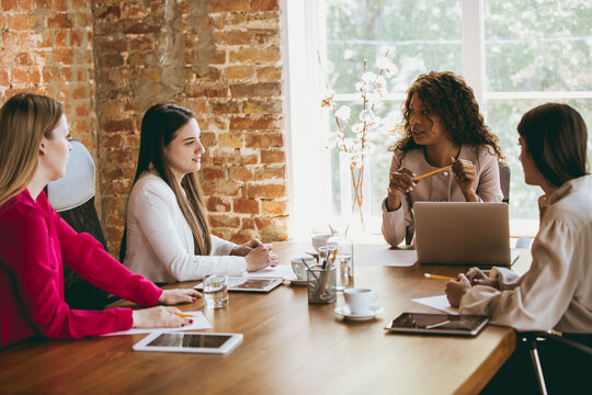 Young caucasian business woman in modern office with team. Creative meeting, tasks giving. Women in front-office working. Concept of finance, business, girl power, inclusion, diversity, feminism.