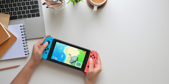 CHIANGMAI, THAILAND - 14 May 2020, Woman playing Animal Crossing New Horizons on Nintendo Switch console on office desk, Nintendo Switch is a popular portable game device now.
