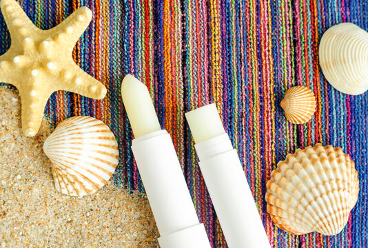 Two lip balms, sunscreen sticks on the colorful beach towel wirh sand and shells. Summer lip treatment and UV protection concept. Close up, copy space