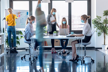 Business young women wearing a hygienic face mask while working in the office. Multiple exposure.
