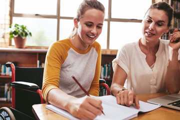 Disabled female student studying with tutor