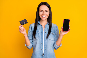 Close-up portrait of nice attractive lovely pretty confident cheerful girl holding hand device plastic card new solution novelty e-banking isolated bright vivid shine vibrant yellow color background
