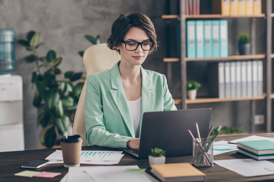 Focused girl agent lawyer manager sit desk chair work laptop have online communication colleagues boss read development company aim progress report wear blazer jacket in workplace workstation