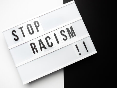 """Light box with the text """"stop racism"""" against black and white background"""