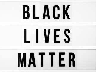 """Light box with the text """"black lives matter"""" against black and white background"""