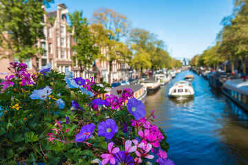 Gracht  Canal in amsterdam netherlands with boats and flowers on a bridge