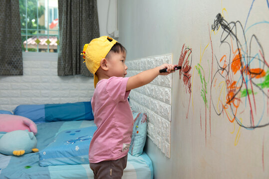 little baby  boy drawing with crayon color on the wall