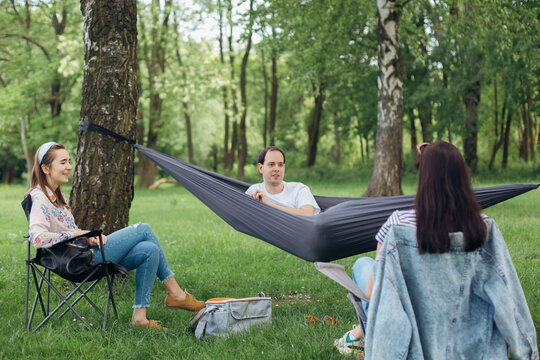 Small group of people enjoying conversation at picnic with social distance in summer park. Social distancing. Friends chilling in hammock and chairs among trees. Lifestyle leisure activity