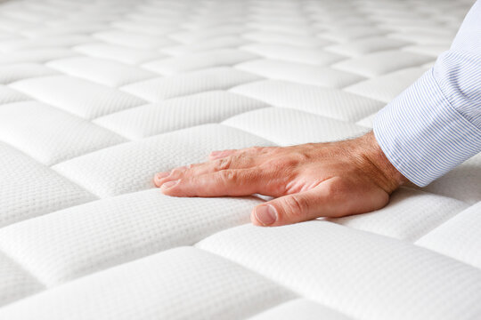 Cropped shot of man testing white orthopedic matress on firmness. Male pressing hypoallergenic foam mattresses surface to check its softness. Close up, copy space, top view, background.
