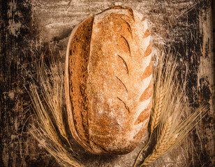 Bakery rustic loaf of bread on cooking background copy space.