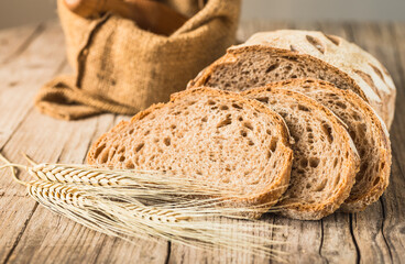 Bakery rustic crusty loaf of bread on rustic wood background.