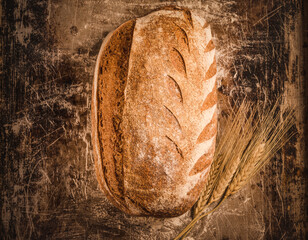 Bakery rustic loaf of bread on rustic cooking background copy space.