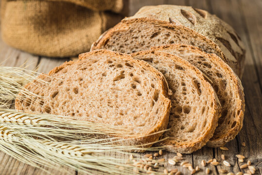 Loaf of bread on rustic wood background copy space.