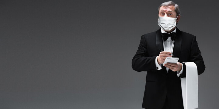 Taking an order. Elegance senior man waiter in protective mask on gray background. Flyer with copyspace. Cafe, restaurant opening. Safety during coronavirus pandemic. Taking care of guests, clients.